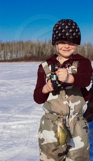 child wearing brown camouflage overall pants holding fishing rod photo