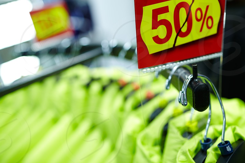 Clothes on hangers in the shop with fifty percent discount. photo