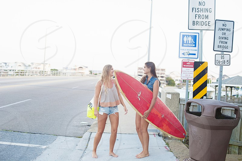 woman carrying red surfboard photo