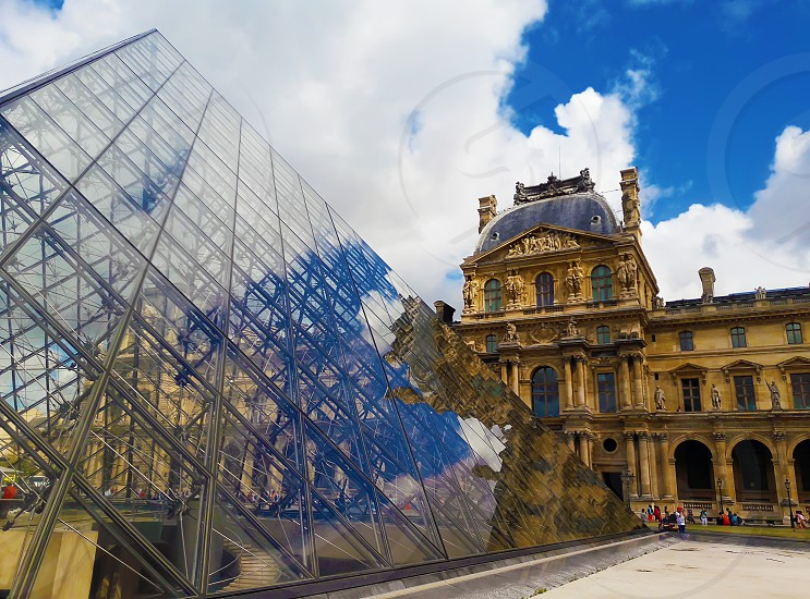 Glass Pyramid in Front of the Louvre Museum with the reflection of the sky in a sunny summer morning. photo