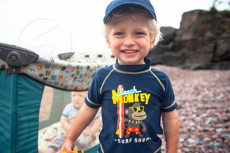 Boy Child Beach Landscape Brothers Crib Rocks Happy Smile Smiling Blonde Hat Cap Swim Ocean Lake Summer Toy Blonde photo