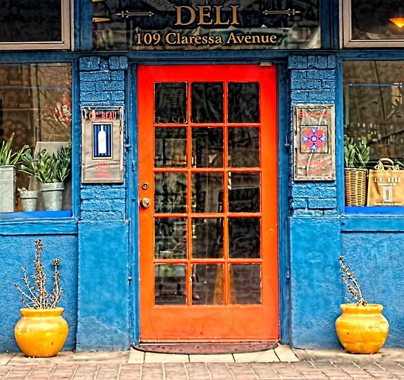 Orange door on a blue painted deli store or shop photo