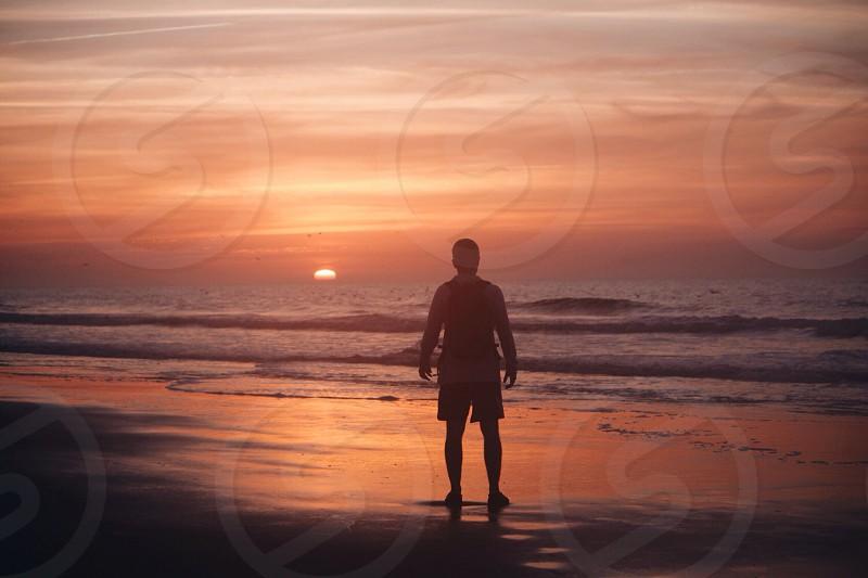 man standing on shore photo