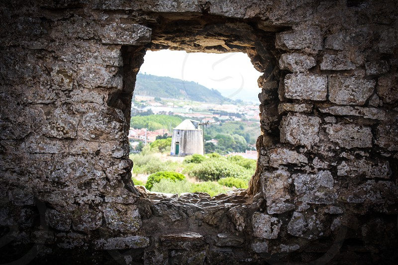 Old Mill seen through a rustic window in Obidos Portugal photo