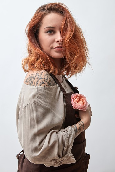 A beautiful girl in an apron holds in her hand a pink flower of a Ranunculus on a gray background. Mother's Day photo