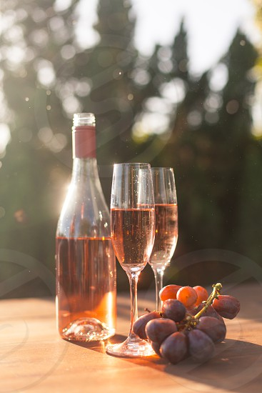 two champagne flutes filled with rose wine on a table next to the bottle and purple table grapes sunder the sun photo