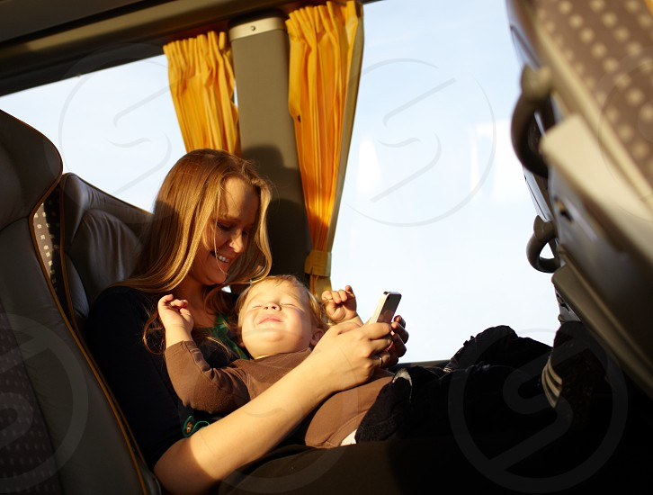 Young mother is playing games on the phone with her son while travelling by bus. Boy is smiling and screwing up his eyes. photo