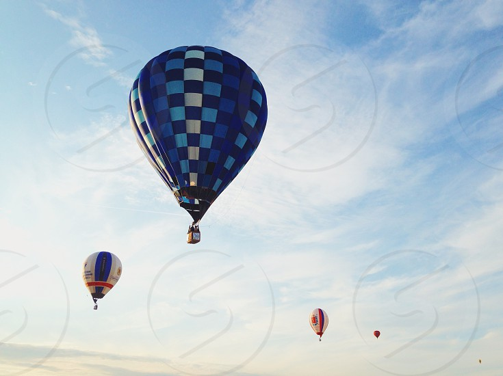 blue white checkered stripe hot air balloons under white cirrus clouds in blue sky photo