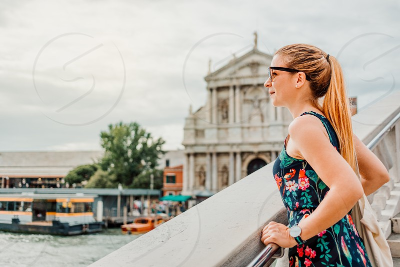 Young woman standing on the bridge in Venice Italy enjoying the view photo
