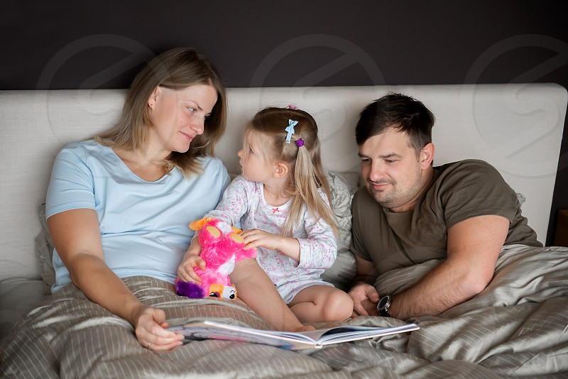 A young family resting in bed at the home photo