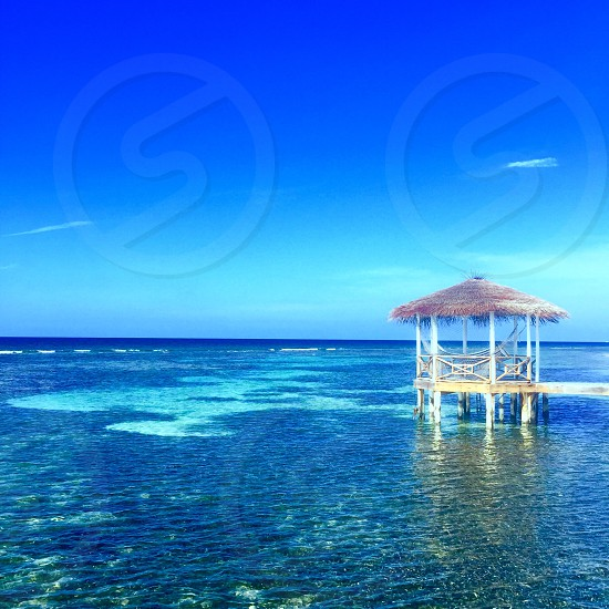 beige and brown gazebo on body of water under clear blue sky during daytime photo