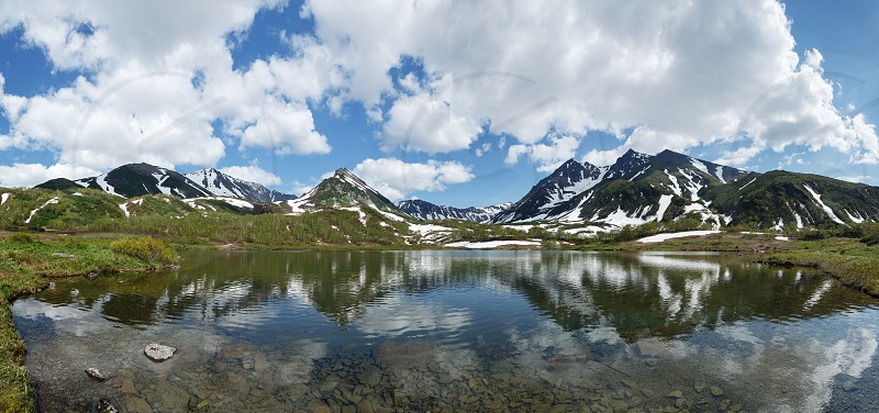 Beautiful landscape of Kamchatka Peninsula: summer panoramic view of Mountain Range Vachkazhets mountain lake and clouds in blue sky on sunny day. Eurasia Russian Far East Kamchatka Region. photo