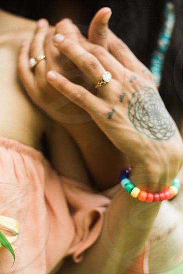 A tattooed hand lovingly-intertwining fingers with another while showing off wedding rings photo