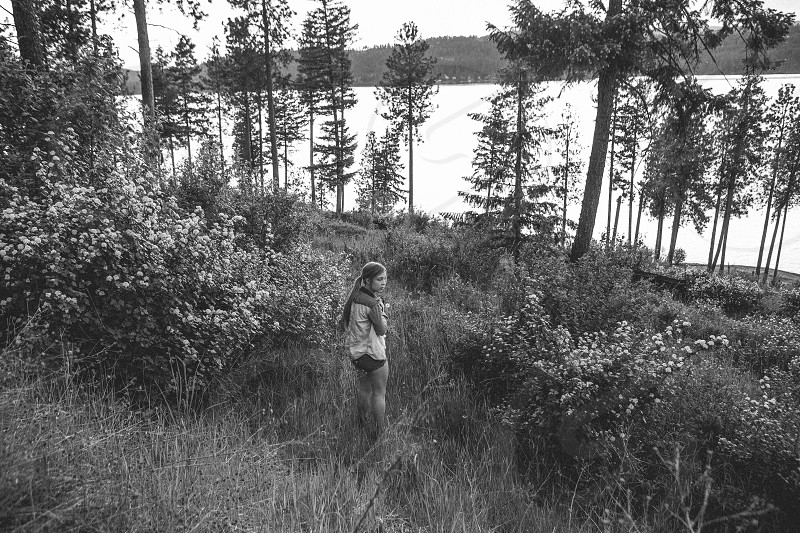 black and white photo of woman standing in forest photo
