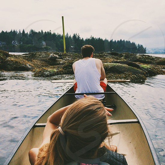 man and woman sitting on grey canoe near grey on rocks and sea photo