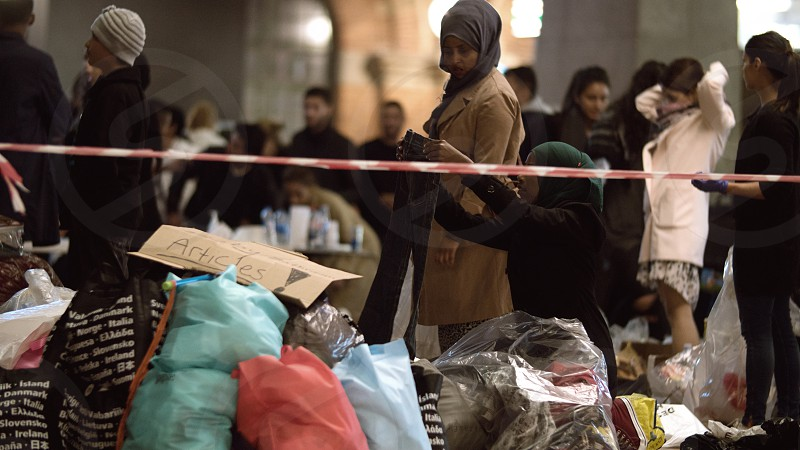 COPENHAGEN DENMARK - SEPTEMBER 15 2015: Female Syrian refugees are picking donated clothes at charity collecting point. They are listening to an announcement made by aid worker. photo