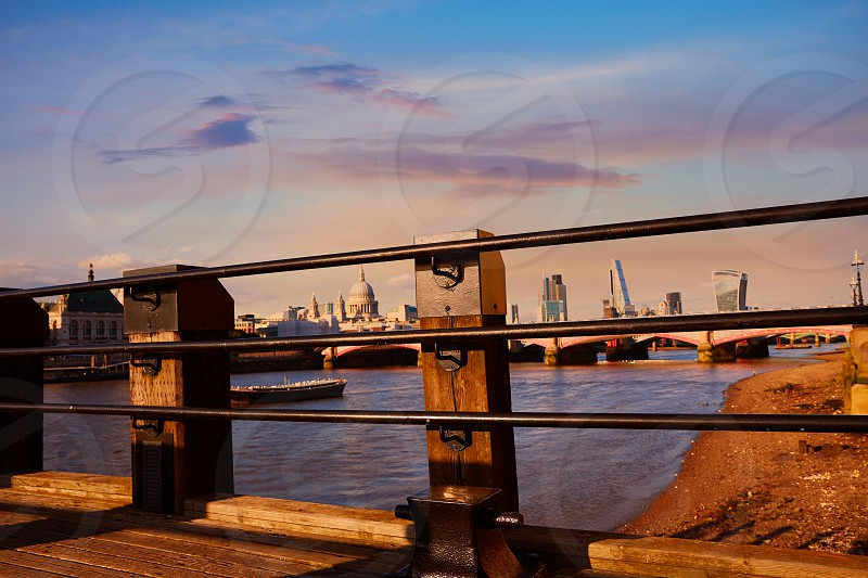 London skyline at sunset from Thames river pier photo