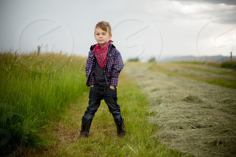 Boy in hay field on the farm with stormy weather. photo