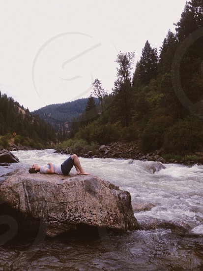 A man on a rock in the middle of a river in Idaho. photo