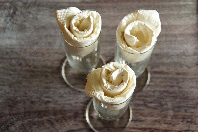 Vanity Fair Square Dinner napkins twisted into roses in champagne flutes on wood table photo
