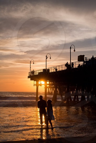 man and woman silhouette on beachfront photo