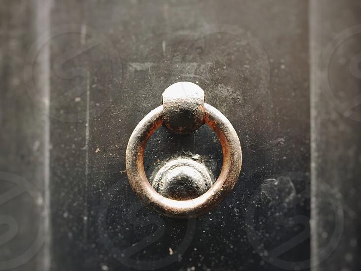 close up of an ancient round clapper on a dark wooden door photo