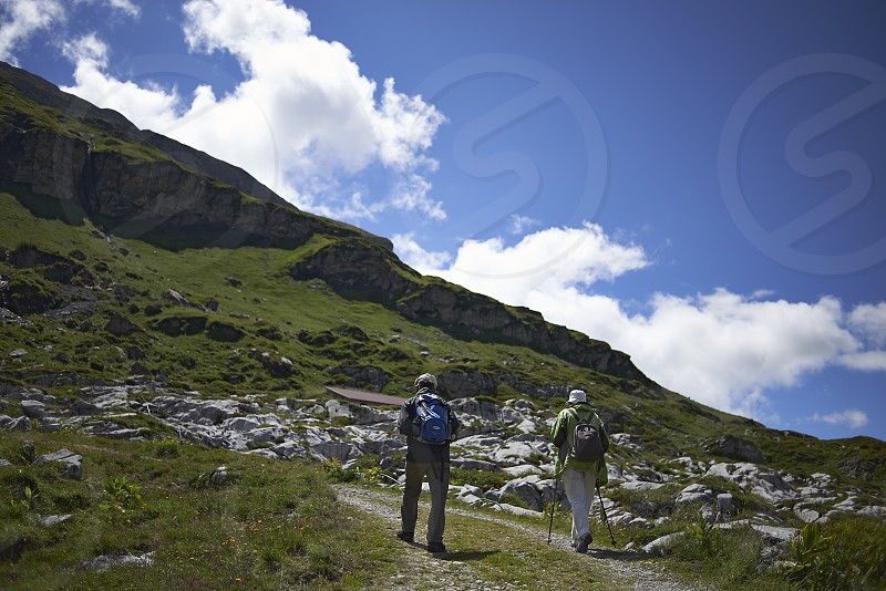 Fit and healthy elderly couple hiking up the mountains in the Swiss Alpes in summer sunshine photo