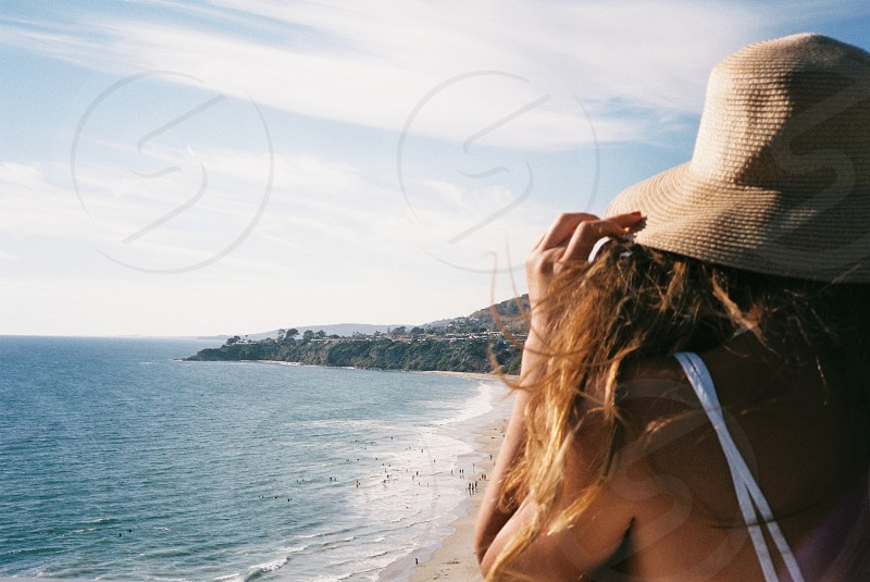 woman in brown sunhat and white spaghetti strap top photo