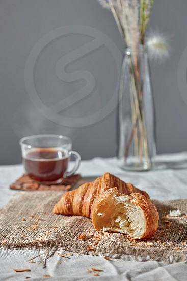 Freshly baked homemade croissants with crumbs on a textile with hot aromatic coffee on a gray textile background. Place for text. Continental breakfast. photo