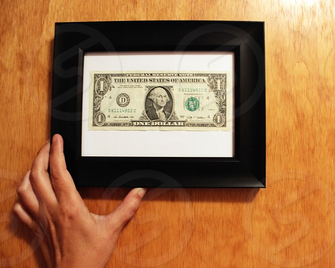 person holding framed of 1 U.S. Dollar bill on brown wooden surface photo