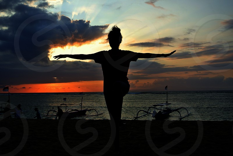 woman doing yoga on the beach photo