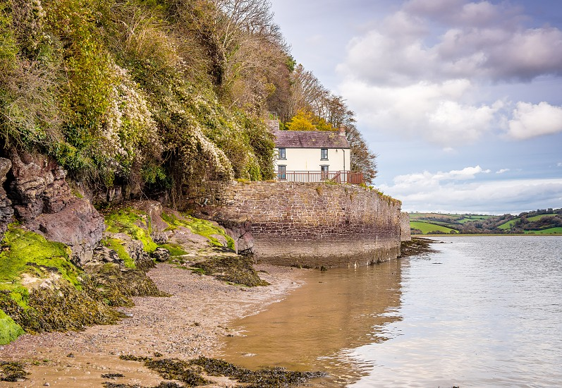 Boathouse at Laugharne - Dylan ThomaThe Boathouse is situated on the estuary at Laugharne in which the poet Dylan Thomas lived with his family between 1949 and 1953 the last four years of his life. It was at this house that he wrote many major pieces. It has often been suggested that he wrote Under Milk Wood whilst living here. The house is set in a cliff overlooking the Tâf Estuary.  photo