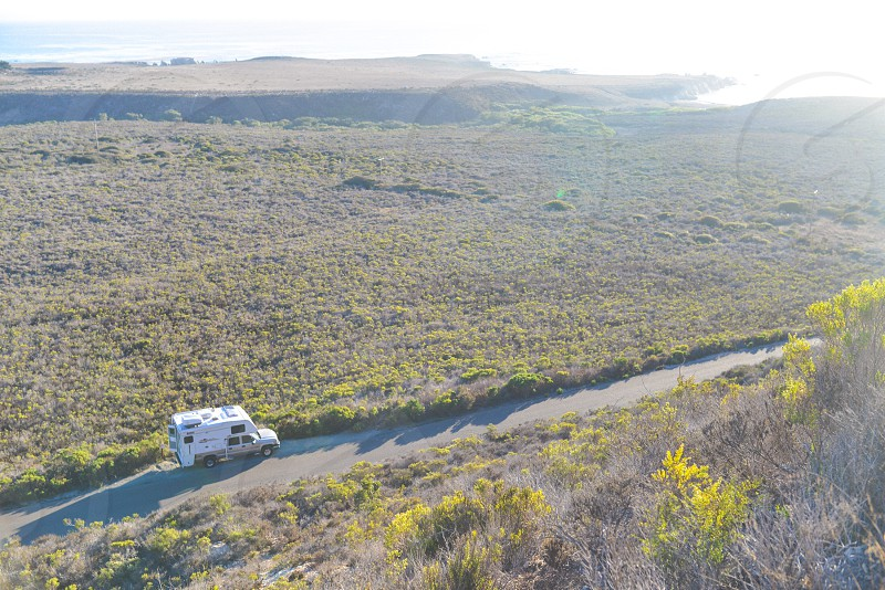 tan pickup truck with white camper top on dirt road photo