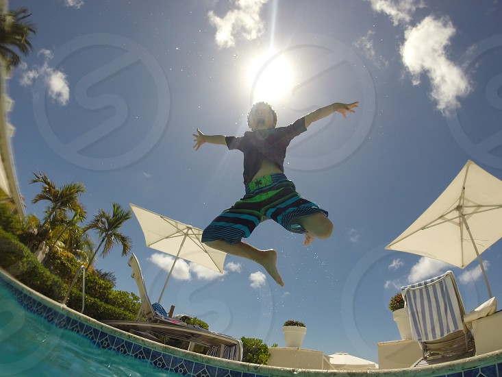 fish eye photo of a boy jumping towards the swimming pool during daytime photo