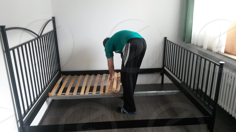 man fixing bed photo