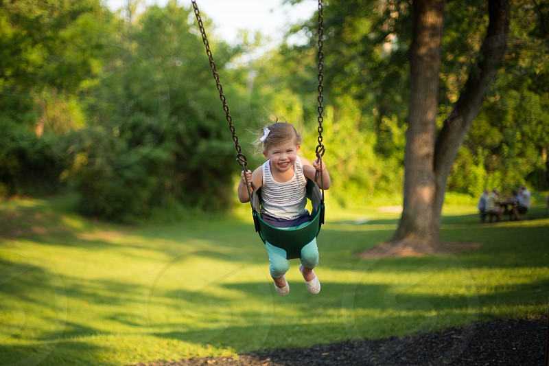 Smiling toddler on a swing at the park photo