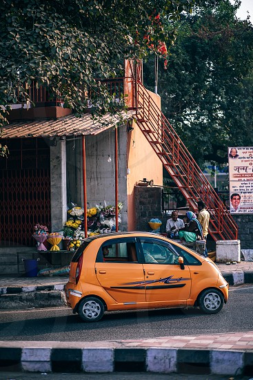 Small orange car about to get on a highway in New Delhi India photo
