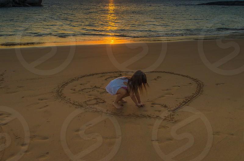 girl writing on brown sand photo