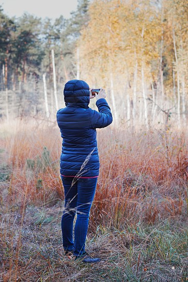 Woman taking photo of forest using camera in mobile phone. Forest in autumn season. Colorful foliage on trees lit by morning sunlight. Natural nature forest landscape in autumn warm sunlight day photo