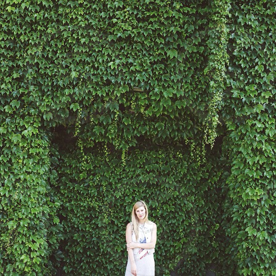 woman in white standing in front of ivy covered wall photo