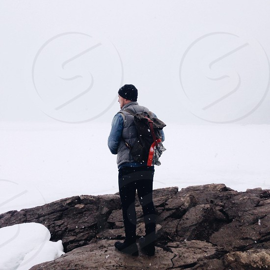 man wearing a black beanie standing on a rock in the snow photo