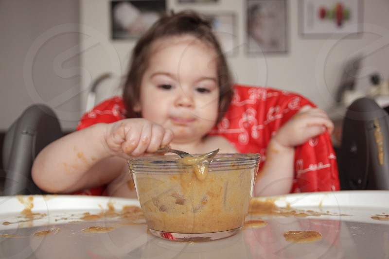 shallow focus photography of brown food on glass bowl eaten by baby on high chair photo