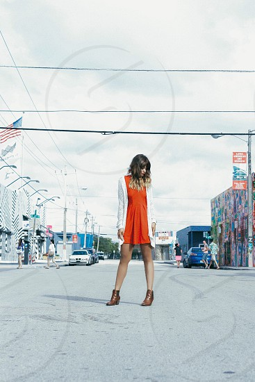 woman in white cardigan and orange dress in the middle of the road photo