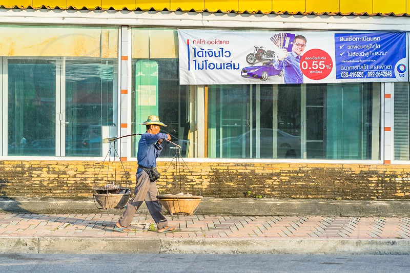 A street hawker walks past a large car finance banner in Thailand. photo