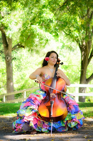 woman in multicolored dress playing cello near green trees during daytime photo