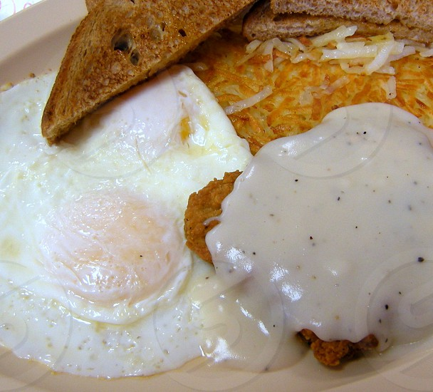 Fried eggs and chicken fried steak with gravy and hashbrowns and toast photo