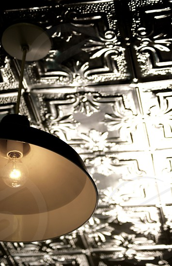 Antique tin ceiling tiles with industrial lighting photo