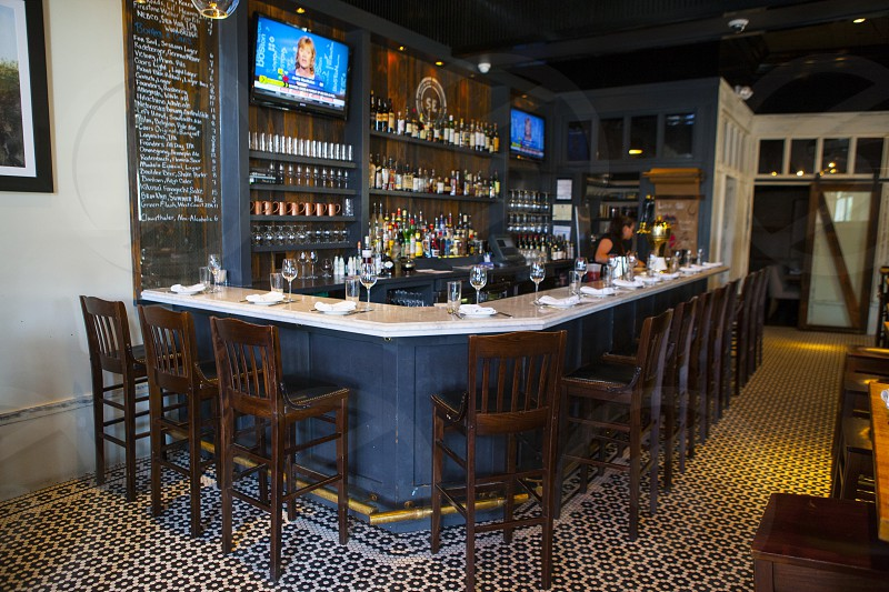 clear wine glass on bar table set near flat screen tv inside the room photo