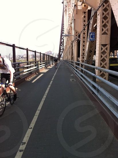 person riding road bike on metal bridge during daytime photo