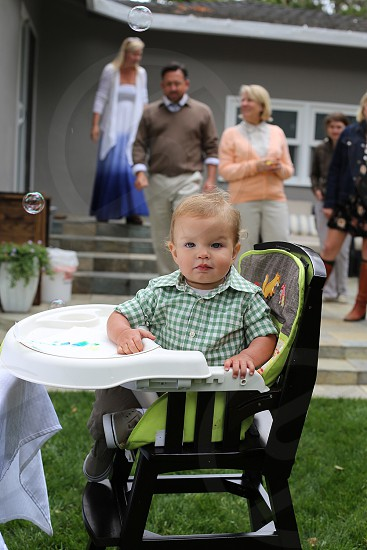 boy in green and white checked shirt on high chair in garden photo